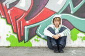 Girl sitting on the floor near graffiti wall — Stock Photo