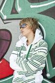 Urban woman wearing glasses stand near graffiti wall — Stock Photo