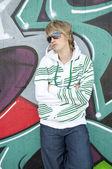 Beautiful girl with big glasses posing near graffiti wall — Stock Photo