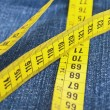 Stock Photo: Blue jeans and measure tape - concept of overweight