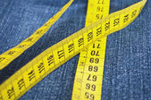 Blue jeans and measure tape - concept of overweight — Stock Photo