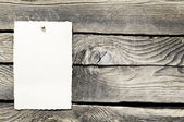 Aged old paper on wood wall — Stock Photo