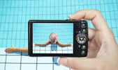 Tourist hand taking photo of woman in swimming pool — Stock Photo