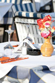 Set table in restaurant with flower — Stock Photo