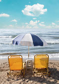 Two loungers under sun umbrella at the beach — Stock Photo
