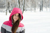 Beautiful girl portrait against winter forest — Stock Photo