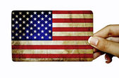 Hand holding grunge card with American flag — Stock Photo