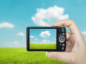 Hand holding digital camera and making landscape photograph — Stock Photo