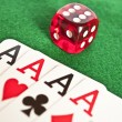 Four aces and red dice on green background — Stock Photo