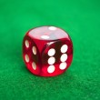 Single red dice on green background — Stock Photo #9337111