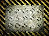 Diamond metal template with yellow warning stripes background — Fotografia Stock