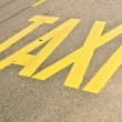 Taxi stand sign painted on the street - Stock Photo