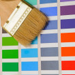 Foto Stock: Palette of color samples with paintbrush on white background