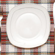 White empty plate with fork and knife on checkered tablecloth — Stock Photo #10081388