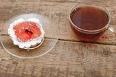 čerstvé koláčky a skleněnou šálek čaje na dřevěný stůl — Stock fotografie