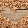 Shape of the heart is made of wheat against a wooden background - Stock Photo