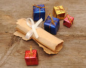 Colorful gift boxes with an old scroll — Stock Photo