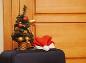 Suitcase and santa hat against a wooden door. — Foto de Stock