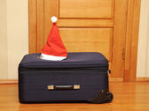 Suitcase and santa hat against a wooden door. — Stock fotografie