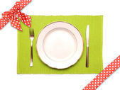 Knife, fork and white plate on a green napkin — Stock fotografie