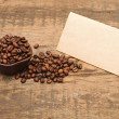 Old paper for recipes and coffee beans on wooden table — Stock Photo