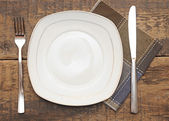 Empty dish, knife and fork and brown napkin on wood table — Stock Photo