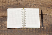 Notepad with pen lying on the wooden table — Stok fotoğraf