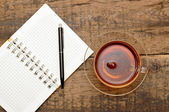 Notebooks, pens, tea on the table — Stock Photo