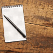 Stock Photo: Blank notepad with pen on wood table