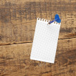 Dart in blank notepad on vintage wooden board — Zdjęcie stockowe #9862881
