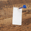 Dart in blank notepad on vintage wooden board — Zdjęcie stockowe #9862918