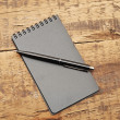 Blank notepad with pen on wood table — Stock fotografie