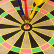 Stock Photo: Cut image of dart pierced on target over dartboard