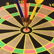 Dartboard with three darts in a bulls eye - Stock Photo