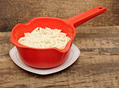 Pasta in red colander on table — Stock Photo