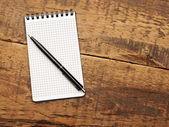 Bloc de notas en blanco con la pluma en la mesa de madera — Foto de Stock