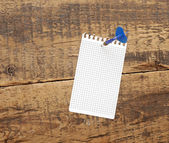 Dart in blank notepad on a vintage wooden board — Stock Photo