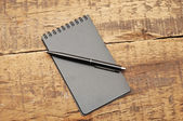Blank notepad with pen on wood table — Stock Photo