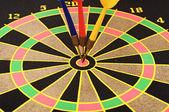 Dartboard with three darts in a bulls eye — Stock Photo