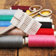 Colorful threads and old scissors on the old wooden table - Foto Stock