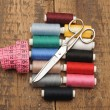 Colorful threads and old scissors on old wooden table — Foto de stock #9890770