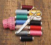 Colorful threads and old scissors on the old wooden table — Stock Photo