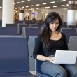 Stock Photo: Womworking with her notebook in airport