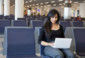 Woman working with her notebook in the airport — Stock Photo