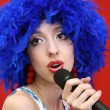 Girl in  bright, blue wig, sings. — Stock Photo
