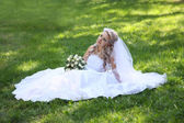 Bride sits on grass. — Stock Photo