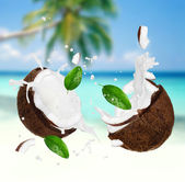 Coconut with milk splash on a beach — Stock Photo
