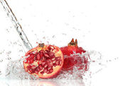 Juicy pomegranate with splashing water — Stock Photo