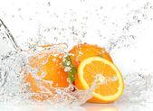 оранжевые фрукты и разбрызгивать воду — Стоковое фото