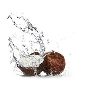 Cracked coconut with milk splash — Stockfoto